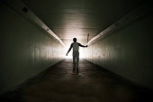 Baseball player walking out of stadium tunnel swinging bat