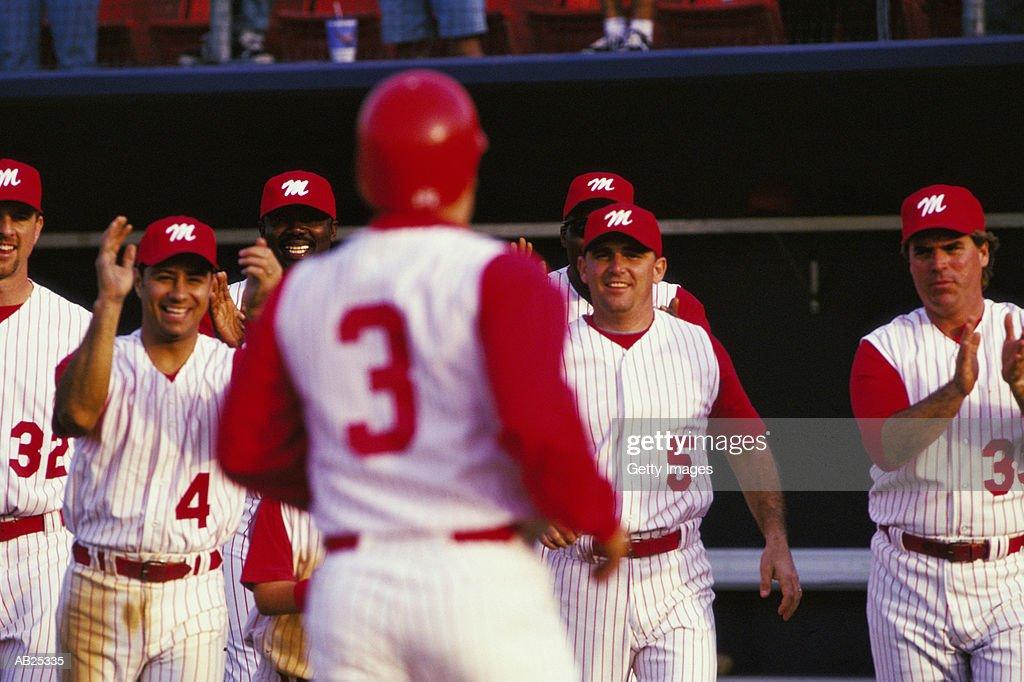 Baseball players applauding team mate : Stock Photo