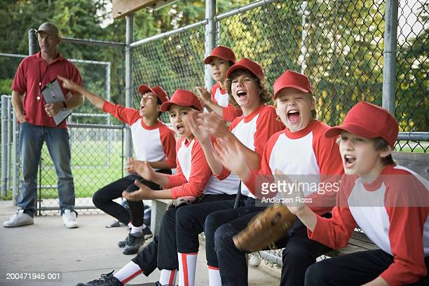 Baseball players (9-14) cheering in dugout, coach in background