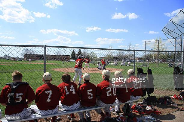 Baseball players on bench watching game through chain