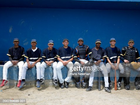 Baseball players sitting in dugout, portrait : Stock Photo