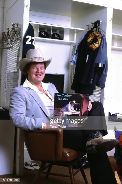 Portrait of National League umpire Joe West posing in cowboy hat while holding a record of his country music album 'Blue Cowboy' during photo shoot...