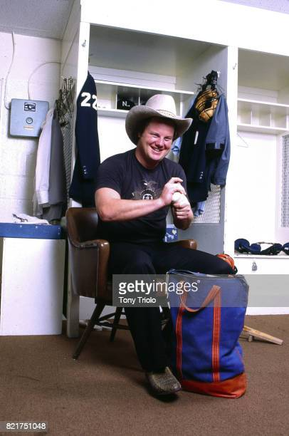 Portrait of National League umpire Joe West posing in cowboy hat and holding baseball during photo shoot in locker room at Shea Stadium Flushing NY...