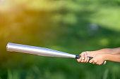Baseball sport concept, hand holding bat on green grass nature background