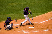 High school baseball player swings at a pitch in a state tournament game.