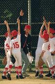Baseball team celebrating with coach