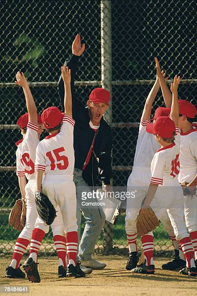 Baseball team celebrating with coach