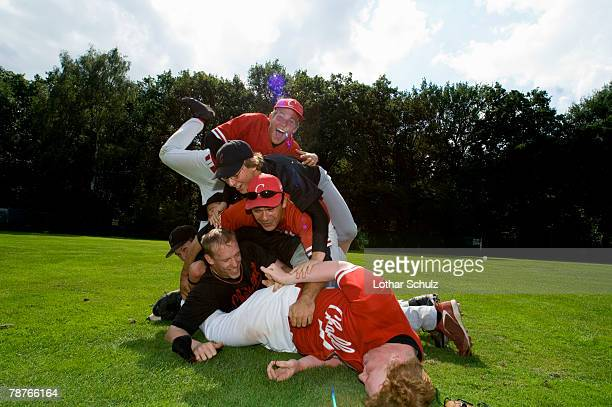 A baseball team piled on top of one another
