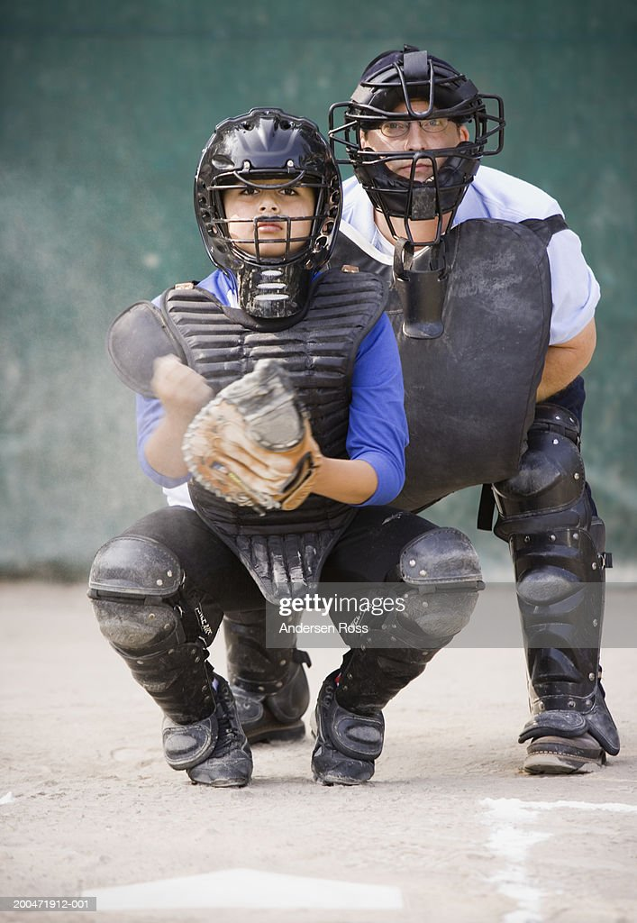 Baseball umpire and catcher (9-11) crouching behind home plate