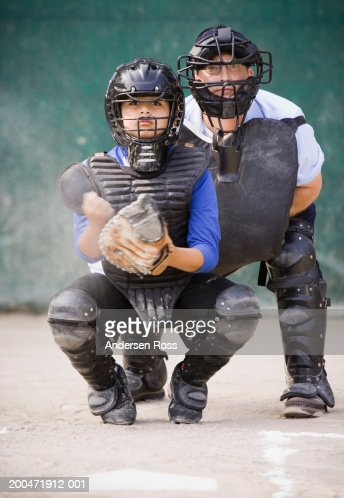 Baseball umpire and catcher (9-11) crouching behind home plate : Stock Photo
