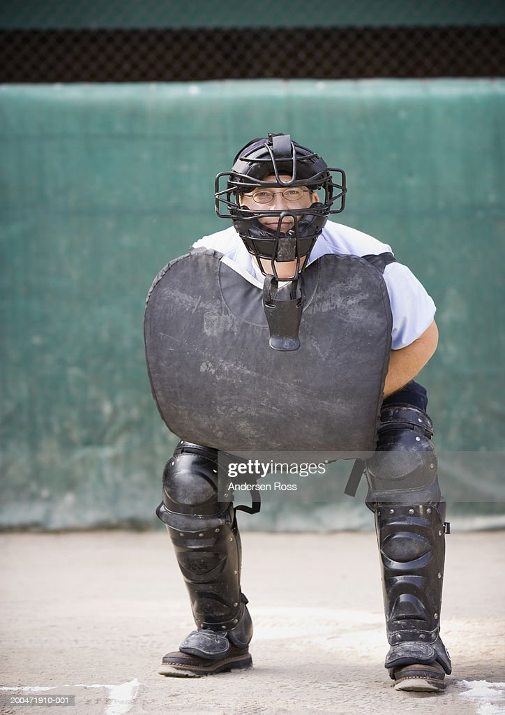 Baseball umpire crouching behind home plate, portrait : Stock Photo