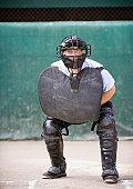 Baseball umpire crouching behind home plate, portrait