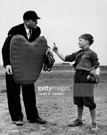 Baseball Umpire Holding Chest Protector Talking With Boy