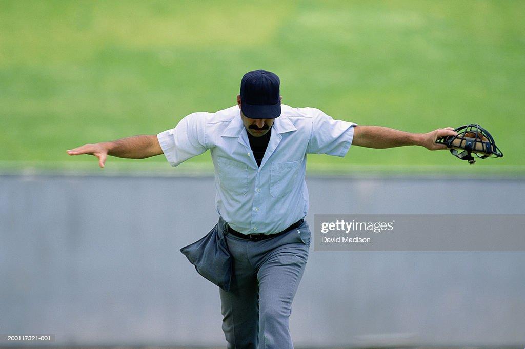 Baseball umpire making 'safe' gesture, looking down