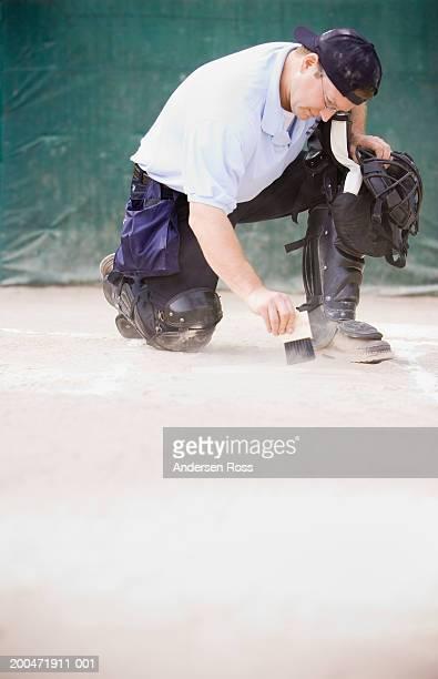 Baseball umpire sweeping home plate