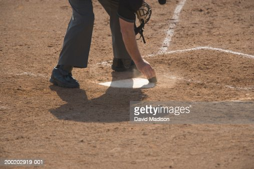 Baseball umpire sweeping off home plate, low section