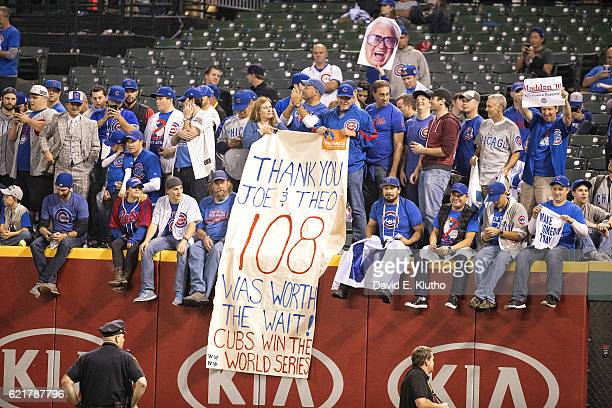 World Series Chicago Cubs fans victorious in stands holding sign reading THANK YOU JOE THEO 108 WAS WORTH THE WAIT after winning Game 7 and...