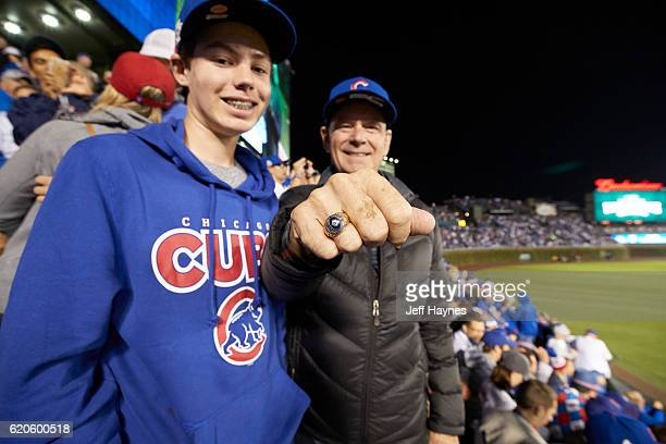 World Series Chicago Cubs young fan with older fan wearing National League Champions ring in stands before game vs Cleveland Indians at Wrigley Field...