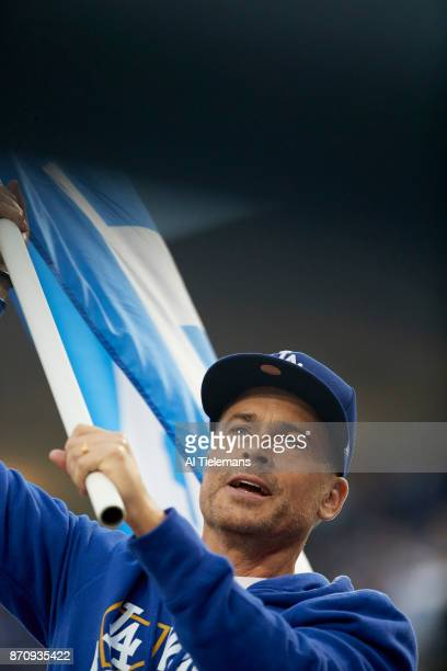 World Series Closeup view of actor and Los Angeles Dodgers fan Rob Lowe waving Dodgers flag before game vs Houston Astros at Dodger Stadium Game 6...