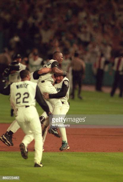World Series Florida Marlins Edgar Renteria victorious with Gary Sheffield lifting him up off field after game winning walkoff hit vs Cleveland...