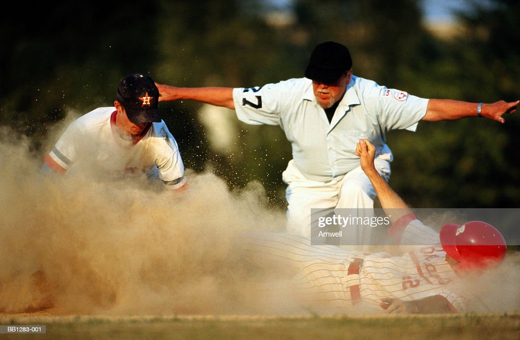 Baseball,player diving for base in cloud of dust,watched by umpire