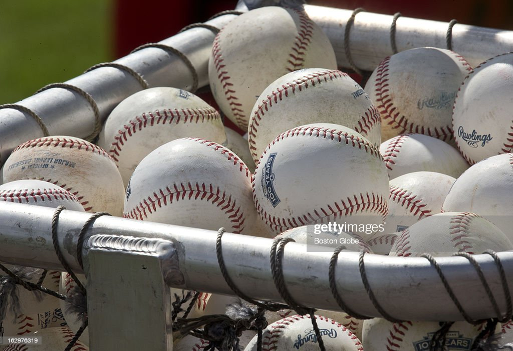 Baseballs are piled in a bucket for batting practice during Boston Red Sox spring training at JetBlue Park on Thursday, Feb. 21, 2013.