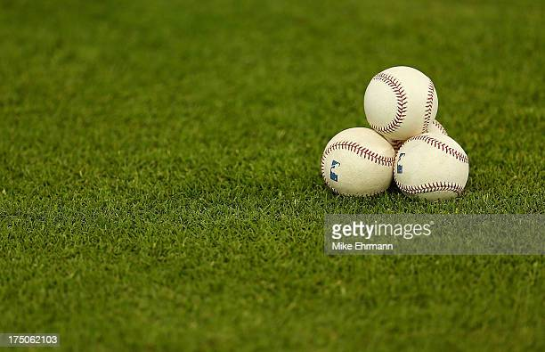 Baseballs sit on the grass before a game between the Miami Marlins and the New York Mets at Marlins Park on July 30 2013 in Miami Florida