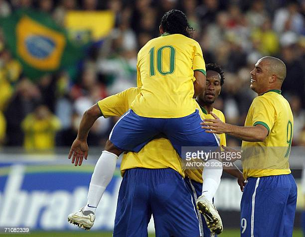 Brazilian footbaler Ronaldinho Gaucho jumps on the back of Adriano celebrating their goal with teammate Ronaldo Nazario against FC Lucern Selection...