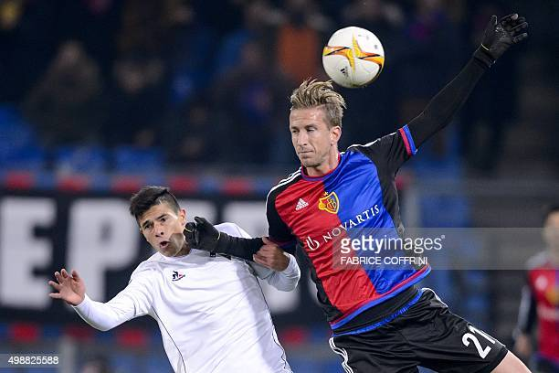 Basel's Austrian forward Marc Janko and Fiorentina's Argentinian defender Facundo Roncaglia go for a header during the UEFA Europa League group I...