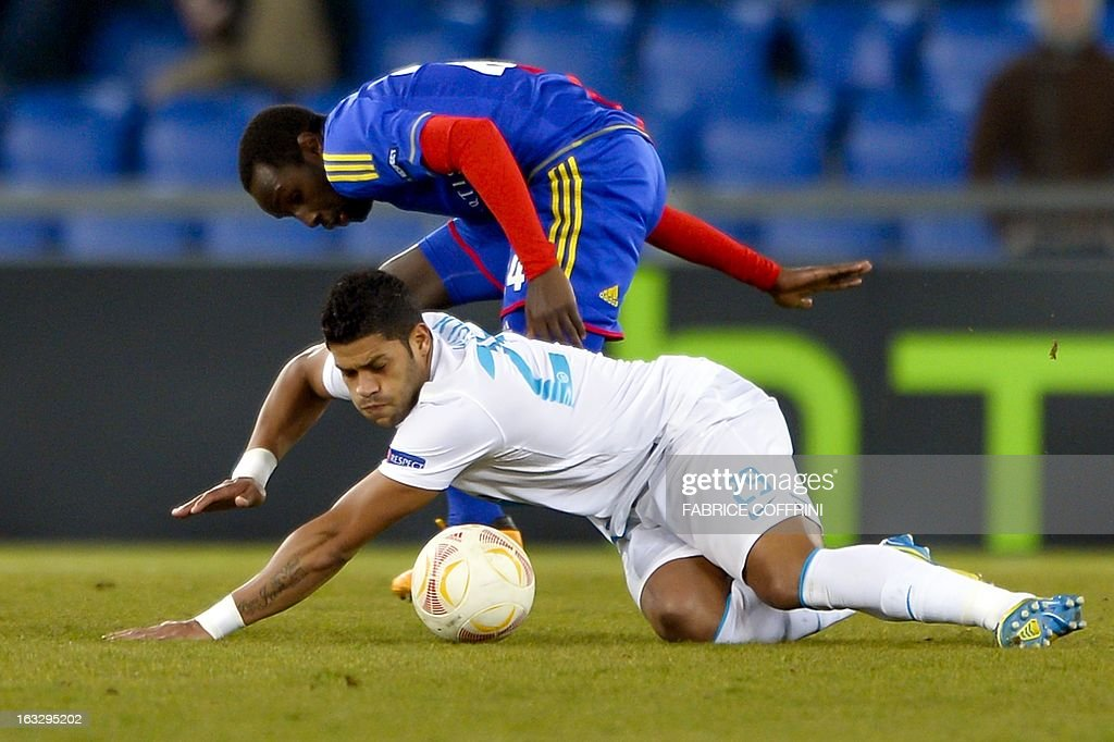 FC Basel's Cameroonian forward Jacques Zoua vies with Zenit St. Petersburg's Brazilian forward Hulk (bottom) during the UEFA Europa League round of 16 first leg football match between FC Basel and Zenit St. Petersburg on March 7, 2013 in Basel. AFP PHOTO / FABRICE COFFRINI