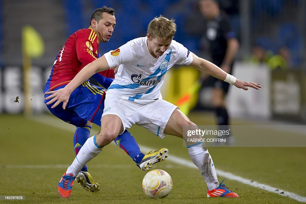 FC Basel's Chilean midfielder Marcelo Diaz (L) vies with Zenit St. Petersburg's Slovakian defender Tomas Hubocan during the UEFA Europa League round of 16 first leg football match between FC Basel and Zenit St. Petersburg on March 7, 2013 in Basel. FC Basel won 2-0. AFP PHOTO / FABRICE COFFRINI