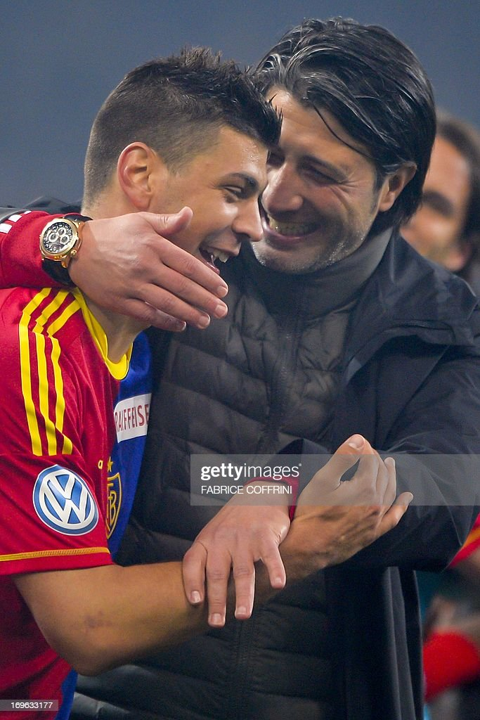 FC Basel's coach Murat Yakin (R) congratulates FC Basel's Serbian defender Aleksandar Dragovic after Basel won the Swiss football championship after their penultimate season's match against Bern Young Boys on May 29, 2013 in Bern. AFP PHOTO / FABRICE COFFRINI