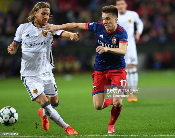 Basel's defender from Switzerland Michael Lang and CSKA Moscow's midfielder from Russia Aleksandr Golovin vie for the ball during the UEFA Champions...