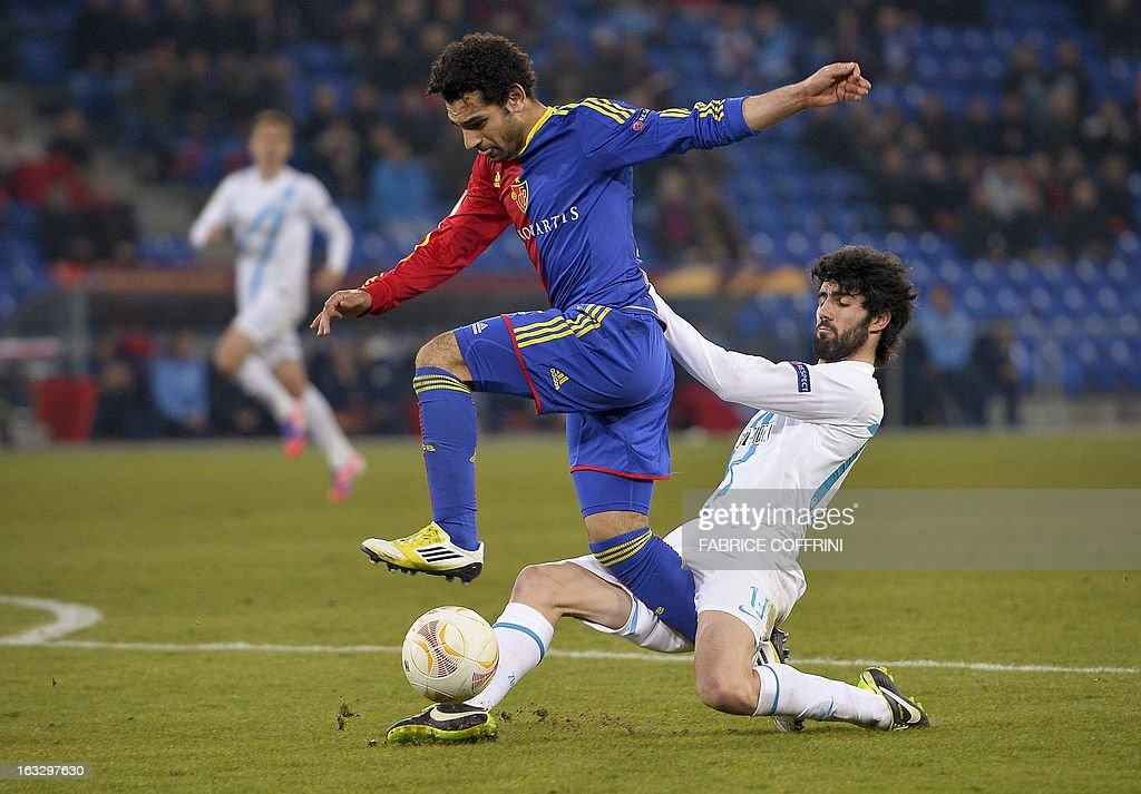 FC Basel's Egyptian midfielder Mohamed Salah (L) is tackled by Zenit St. Petersburg's Portugese defender Luis Neto during the UEFA Europa League round of 16 first leg football match between FC Basel and Zenit St. Petersburg on March 7, 2013 in Basel. FC Basel won 2-0. AFP PHOTO / FABRICE COFFRINI