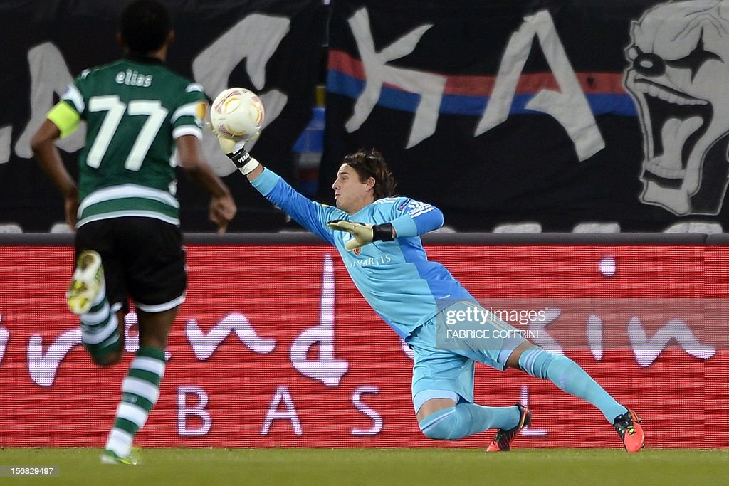 FC Basel's goalkeeper Yann Sommer (C) deflects the ball next to Sporting's Brazilian midfielder Elias during their Europa League UEFA Europa League Group G football match between FC Basel and Sporting Clube de Portugal on November 22, 2012 in Basel. COFFRINI