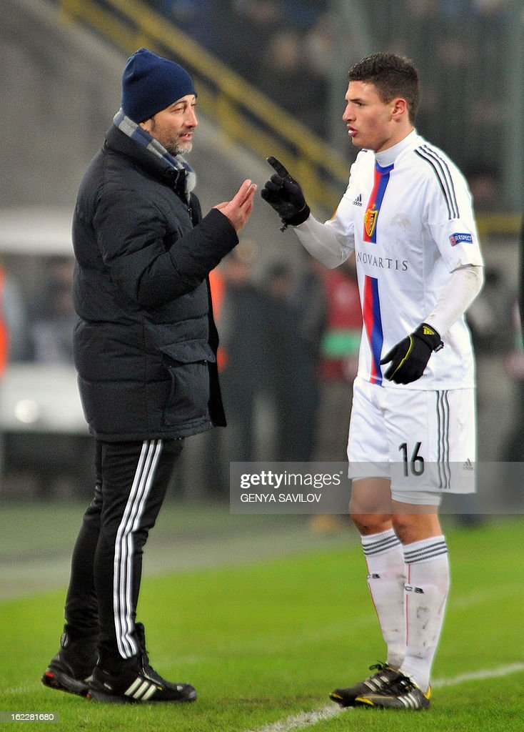 Basel's head coach Murat Yakin (L) speaks with player Fabian Schar (R) during the UEFA Europa League, Round 32, football match against FC Dnipro in Dnipropetrovsk on February 21, 2013. AFP PHOTO/ GENYA SAVILOV