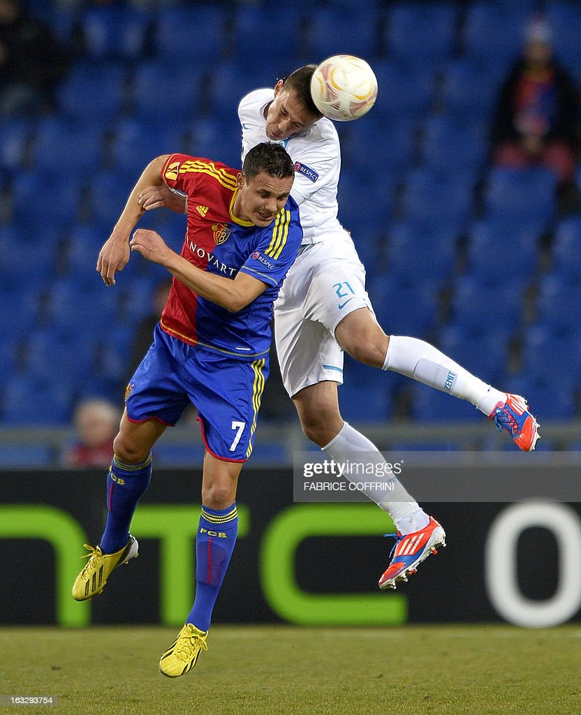 Basel's midfielder David Degen (L) vies with Zenit St. Petersburg's Serbian defender Milan Rodic during the UEFA Europa League round of 16 first leg football match between FC Basel and Zenit St. Petersburg on March 7, 2013 in Basel. AFP PHOTO / FABRICE COFFRINI