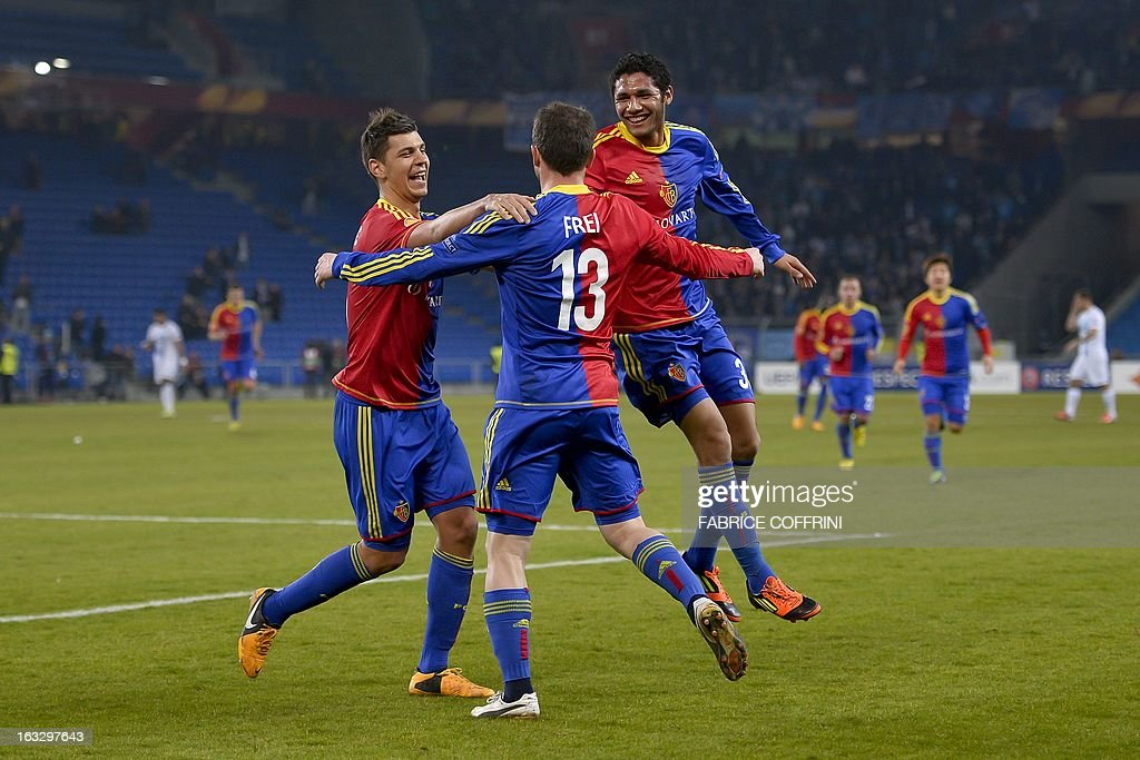 FC Basel's Serbian defender Aleksandar Dragovic (L) and teammate Egyptian midfielder Mohamed Elneny (R) celebrate the penalty scored by teammate forward Alexander Frei (C) during the UEFA Europa League round of 16 first leg football match between FC Basel and Zenit St. Petersburg on March 7, 2013 in Basel. FC Basel won 2-0. AFP PHOTO / FABRICE COFFRINI