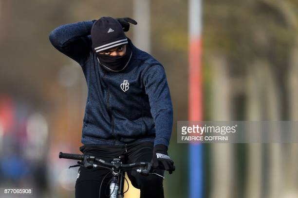 Basel's Swiss defender Manuel Akanji arrives riding a bicycle for a training session on the eve of the UEFA Champions League Group A football match...