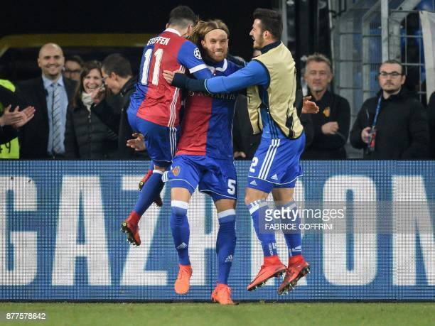 Basel's Swiss defender Michael Lang celebrates with teammates after scoring a goal during the UEFA Champions League Group A football match between FC...