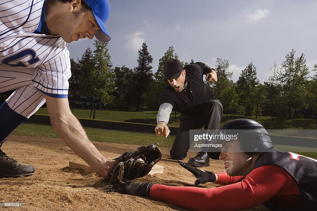 Baseman tagging and umpire signaling strike out to baseball player