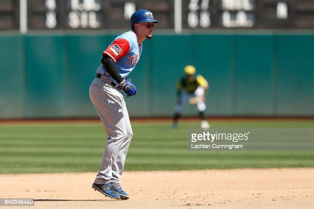 Baserunner Ryan Rua of the Texas Rangers takes a lead off of second base in the fourth inning against the Oakland Athletics at Oakland Alameda...