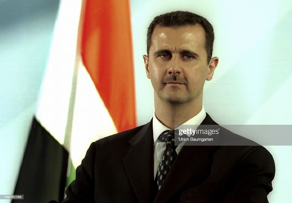 Bashar AL-ASSAD, state president of Syria, in front of the Syrian flag.
