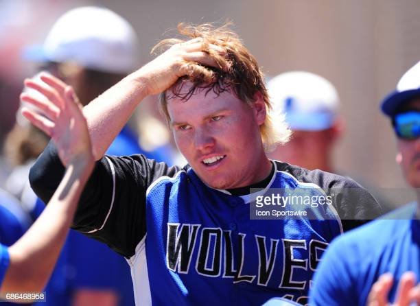 Basic Academy Wolves batter Jack Wold high fives teammates in the dugout after scoring a run against the Galena Grizzlies in the fifth inning of the...