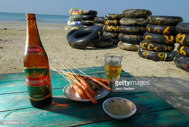 A basic lunch of grilled shrimp and Myanmar Beer as served along Chaungtha Beach a popular spot for foreign tourists as well as Burmese tourists from...