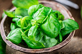 Portion of fresh Basil leaves (selective focus; close-up shot) on wooden background