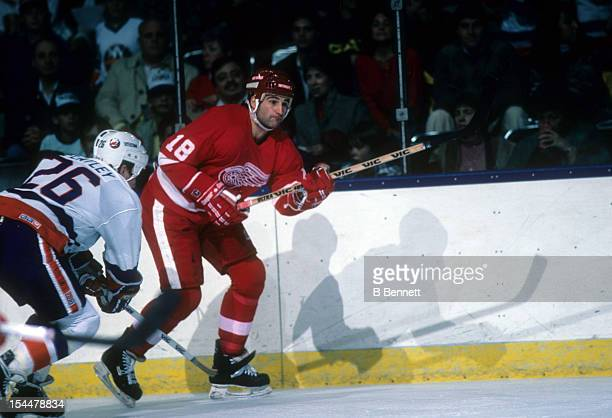 Basil McRae of the Detroit Red Wings skates on the ice as Pat Flatley of the New York Islanders looks to check him on November 8 1986 at the Nassau...