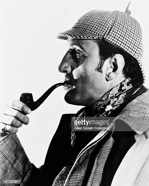 Basil Rathbone British actor wearing a deerstalker hat and smoking a pipe in profile in a studio portrait against a white background circa 1945...