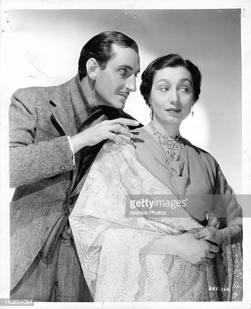 Basil Rathbone getting up close to Aline MacMahon in a scene from the film 'Kind Lady' 1935
