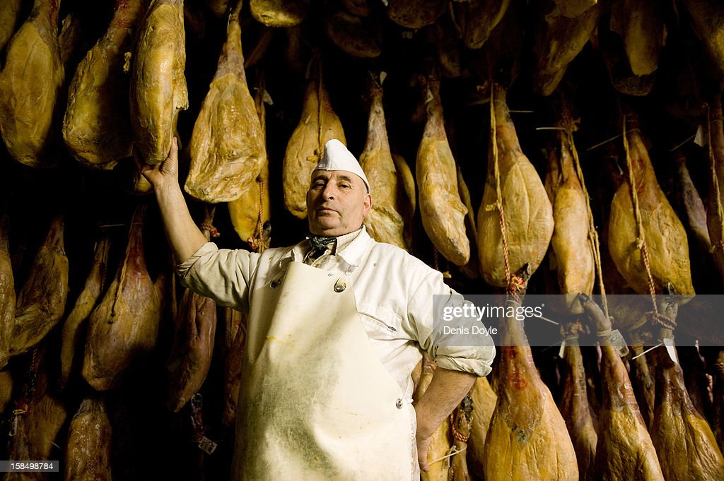 Basilio Hoyos, manager of the Sociedad Chacinera Albercana Cooperative is photographed beside leg of dry-cured Jamon Iberico de bellota (acorns) in the village of La Alberca on December 14, 2012 near Salamanca, Spain. Dry-cured Iberian ham or Jamon Iberico de Bellota is a favourite amongst Spaniards and producers are hoping for improved sales over the busy christmas period. The jamon Iberico de Bellota are usually dry-cured for up to three years after the pigs have been few on a diet of acorns in the last three months of their lives.